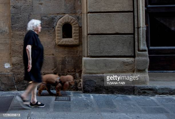 """Woman and her dog walk past a """"buchetta del vino"""" a small window to serve wine a tradition which exists since the Renaissance period and that is..."""
