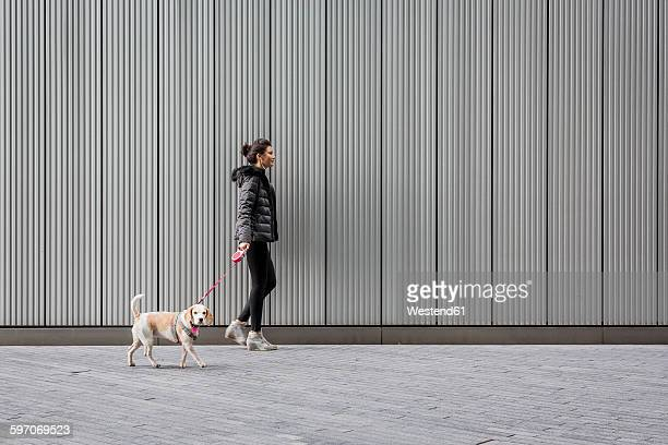 Woman and her dog walking on pavement in front of a metal facade