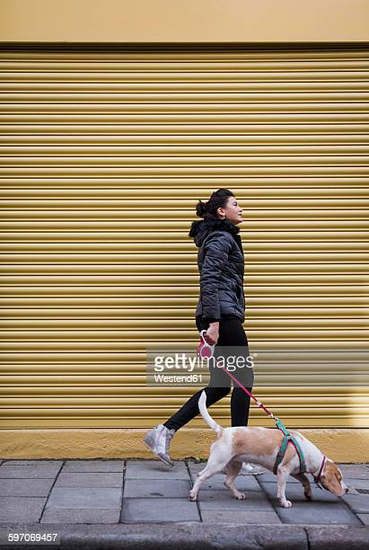 Woman and her dog walking on pavement in front of a roller shutter
