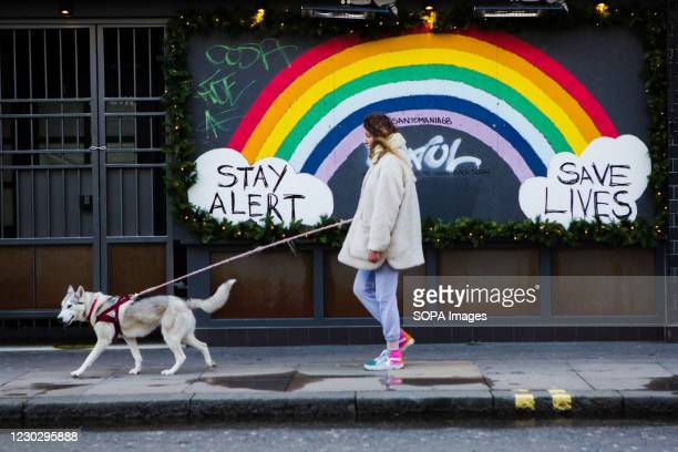 Woman and her dog walking past the Stay Alert Save Lives Rainbow Sign in Soho during Christmas Eve 2020.
