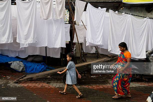 A woman and her girl child walk past drying clothes at an openair laundromat near Cuffe Parade in South Mumbai