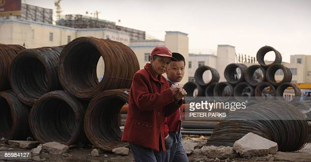 A woman and her grandson walk past rolls of steel in a industrial park in Hohhot in China's Inner Mongolia region on April 14 2009 China's industrial...