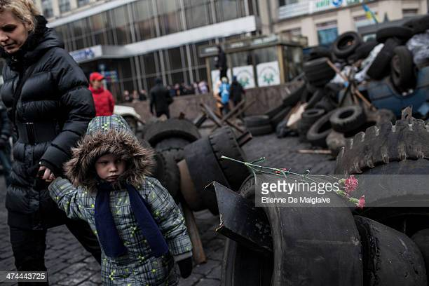 A woman and her kid walk by carnations layed on a pile of tires that were used in fire barricades in previous clashes with riot police as a makeshift...