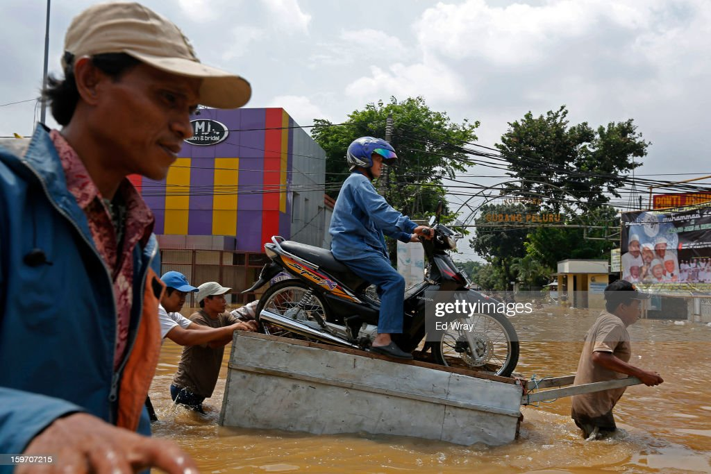 A woman and her motorbike are transported over a flooded road on a makeshift raft on January 19, 2013 in Jakarta, Indonesia. Floodwaters receded today after three days of heavy flooding which left thousands of people's homes underwater. According to Indonesian police the death toll has reached 15.