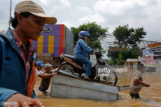 Woman and her motorbike are transported over a flooded road on a makeshift raft on January 19, 2013 in Jakarta, Indonesia. Floodwaters receded today...