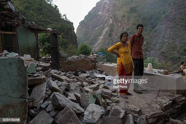 A woman and her son are pictured standing inside their collapsed house on the Araniko Road near the Kobani Village Isolated Nepalese Villagers still...