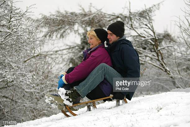 Woman and her son go tobogganing in a park on January 8, 2003 in Carshalton, England. Heavy snowfall has caused chaos across the South East and...