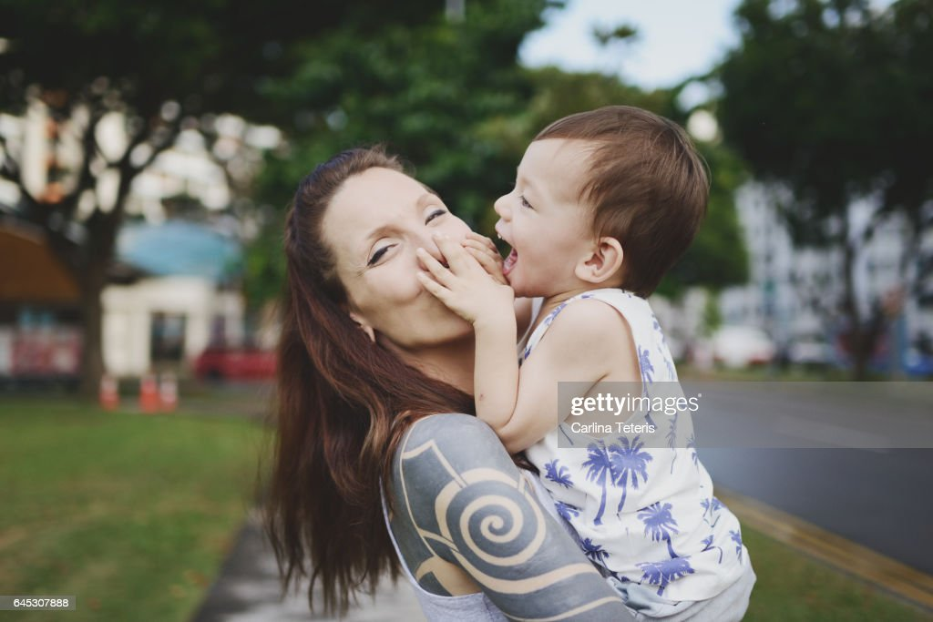 Woman and her son having fun in a city park : Stock Photo