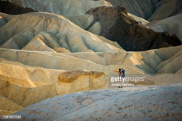 a woman and her son hiking through dramatic mountains in death valley - death valley national park stock pictures, royalty-free photos & images