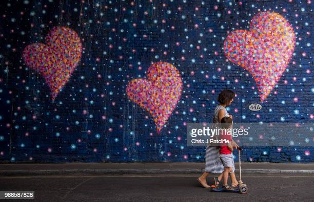 A woman and her son walk past a mural in a tunnel near Borough Market painted by graffiti artist James Cochran also known as Jimmy C that...