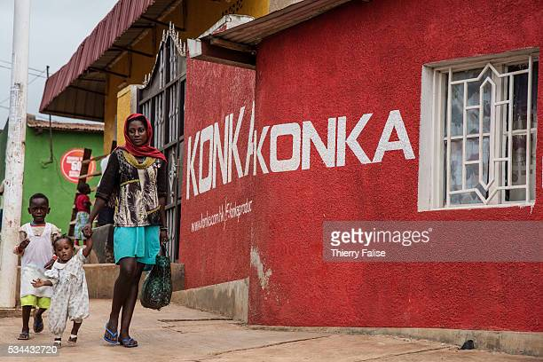 A woman and her two children walk past a wall painted with an advertisement for a brand of camera and films in a popular district of Kigali Kigali...
