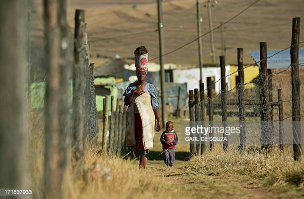 A woman and her young child are pictured on June 26 2013 in Qunu the village where former South African President Nelson Mandela grew up Mandela's...