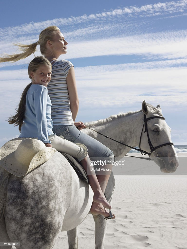 Woman and Her Young Daughter Ride a White Horse on the Beach : Stock Photo