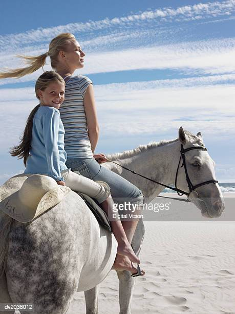 Woman and Her Young Daughter Ride a White Horse on the Beach