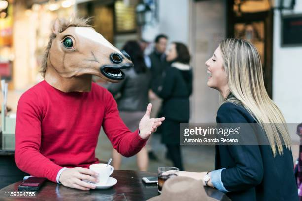 woman and horse face man with costume drinking coffee in bar terrace and talking having fun - mask joke stock pictures, royalty-free photos & images