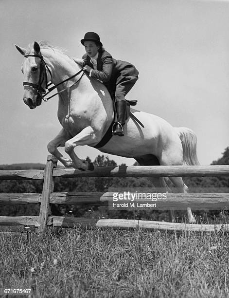 woman and horse jumping fence  - {{ contactusnotification.cta }} stockfoto's en -beelden