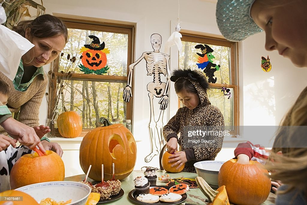 Woman and kids carving pumpkins : Stock Photo