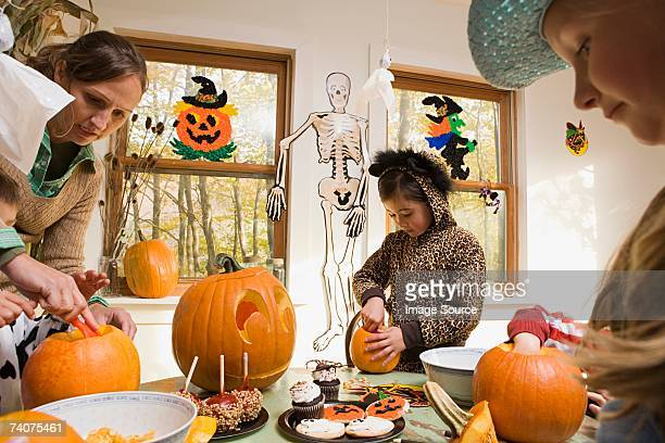 woman and kids carving pumpkins - halloween party stock photos and pictures