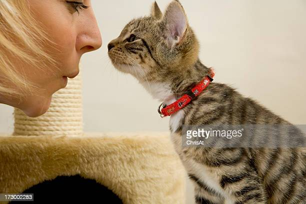 Woman and kitten touching noses