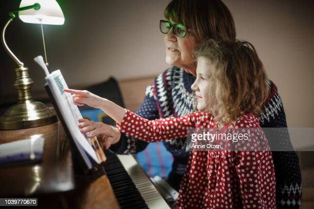 woman and little girl look at a piano book together - pianist front stock pictures, royalty-free photos & images