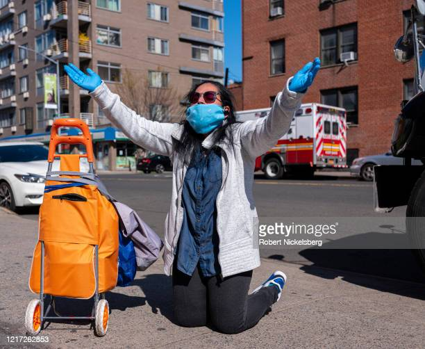 A woman and local resident Amella kneels as she prays for the victims of the coronavirus outside the emergency room of the Elmhurst Hospital Center...