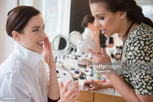 Woman and makeup artist using cell phone