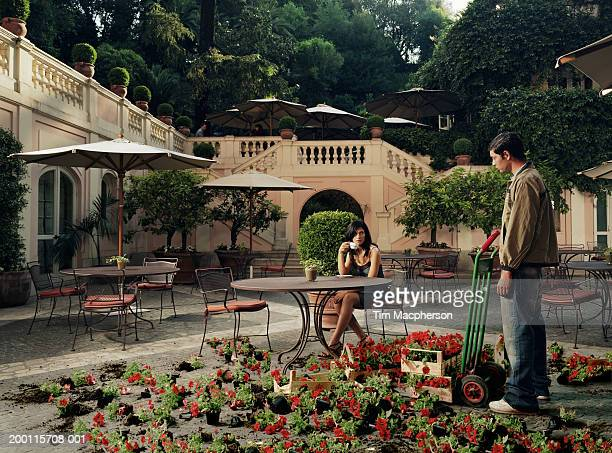 Woman and male flower seller outside cafe looking at one another