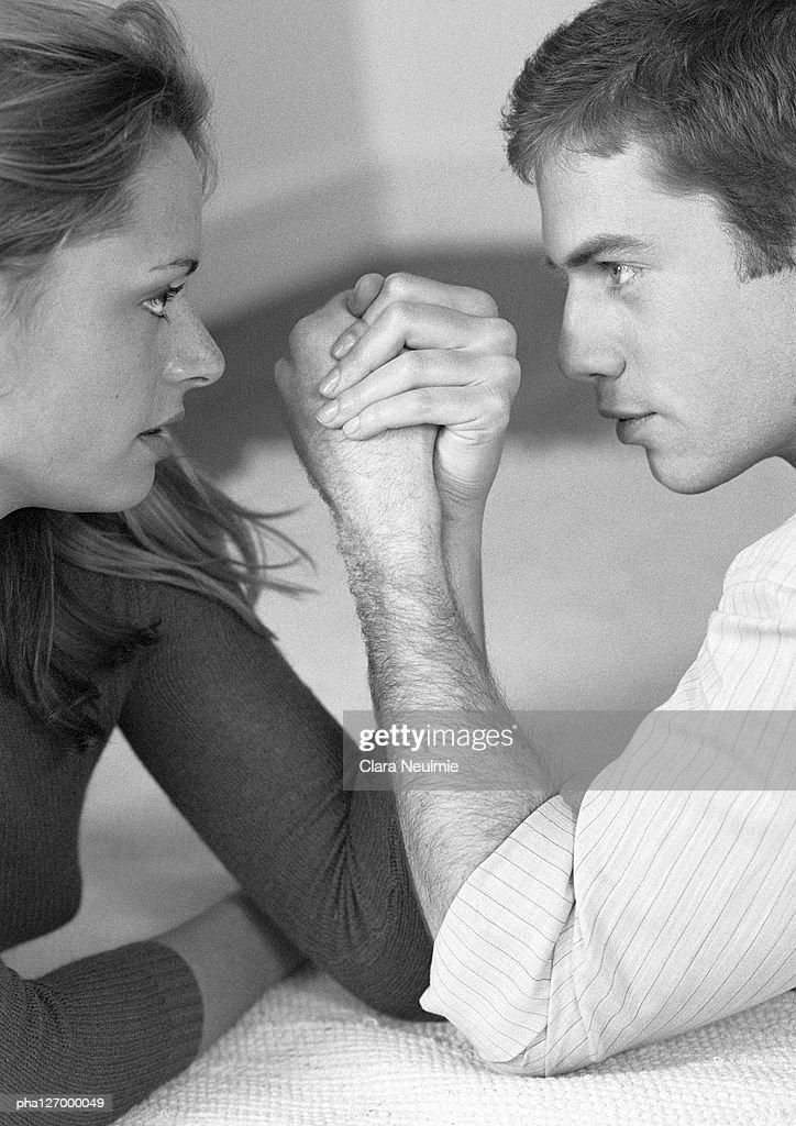 Woman and man arm wrestling, close-up, b&w : Stockfoto