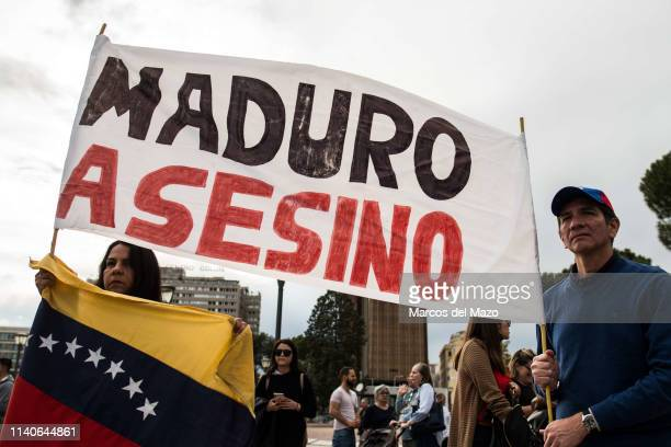 """Woman and man carry a banner with the words 'Maduro murderer"""" during a protest against Venezuelan president Nicolas Maduro and supporting Juan..."""