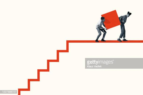 woman and man carrying large block on staircase - dedication stock pictures, royalty-free photos & images