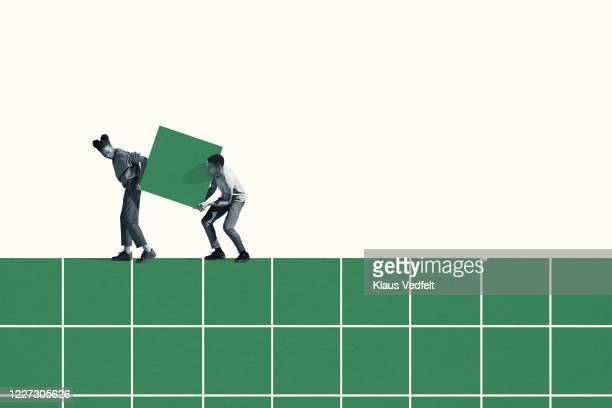woman and man carrying large green block on grid - soporte conceptos fotografías e imágenes de stock