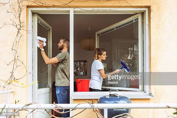 Woman and man cleaning window together