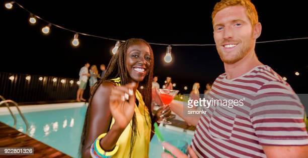 woman and man dancing at party by pool at night - martini glass stock pictures, royalty-free photos & images