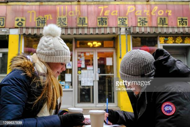 Woman and man dine in an outdoor seating area at Nom Wah Tea Parlor in Manhattan's Chinatown during the coronavirus pandemic on January 31, 2021 in...