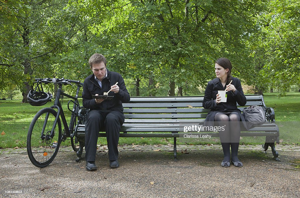 Woman and man eating lunch on park bench : Stock-Foto