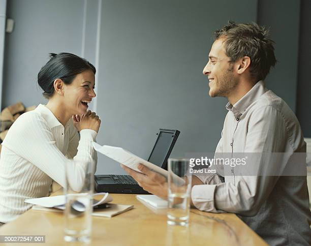 Woman and man having meeting in cafe, smiling, side view