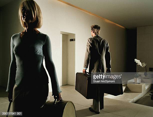woman and man holding luggage facing opposite directions in lobby - older women in short skirts stock pictures, royalty-free photos & images