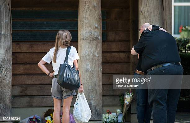 A woman and man hug next to floral tributes left by familys and members of the public to victims of the 9/11 terroism attacks at the September 11...