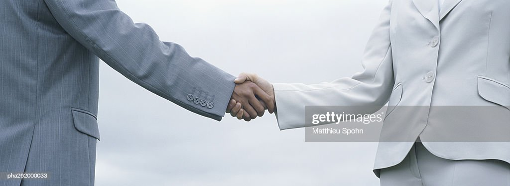Woman and man in suits shaking hands, mid-section with sky in background : Stockfoto