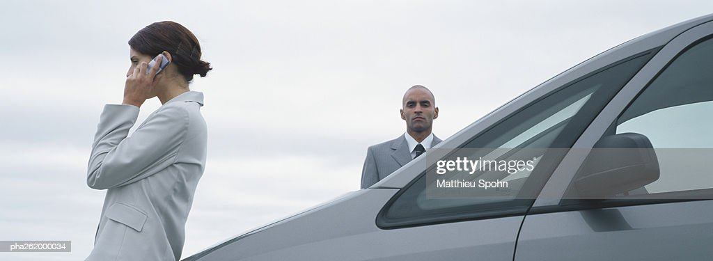 Woman and man in suits standing near car, man looking at camera, woman talking on cell phone : Stockfoto