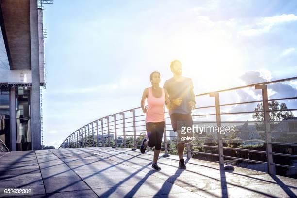woman and man jogging over berlin bridge at sunset