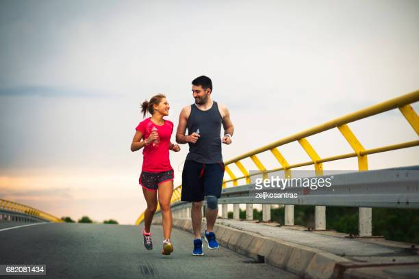 woman and man jogging together - spring racing stock photos and pictures