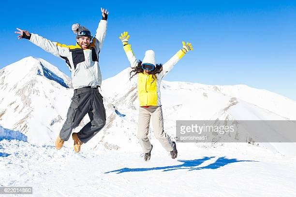 Woman and man jumping in the air on snow mountain