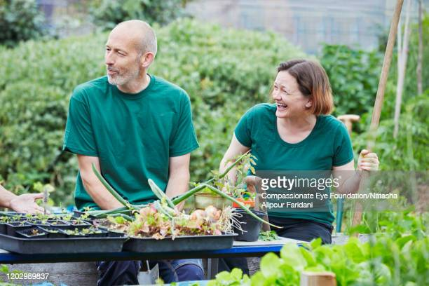 woman and man laughing in community garden - compassionate eye foundation stock pictures, royalty-free photos & images