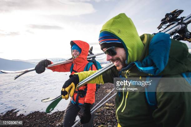 woman and man laughing while walking with skis in iceland - ski holiday stock pictures, royalty-free photos & images