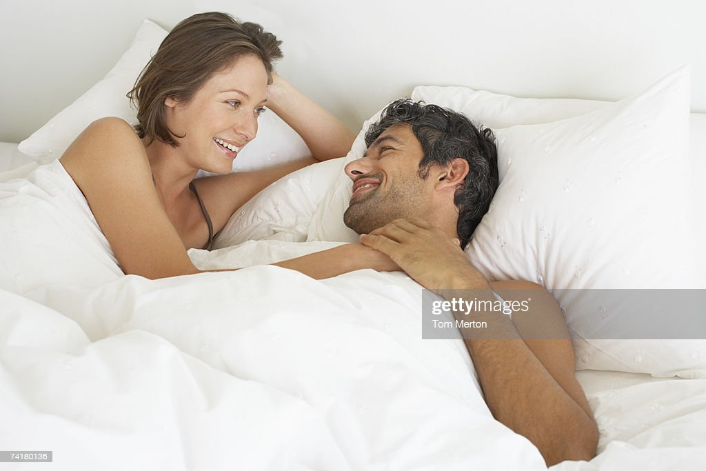 Woman and man lying down in bed : Stock Photo