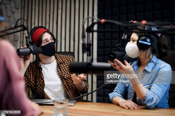 woman and man makes a podcast audio recording in a studio, coronavirus concept. - radio stock pictures, royalty-free photos & images