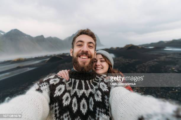 woman and man making selfie near  vestrahorn mountains near the sea - knitted stock pictures, royalty-free photos & images
