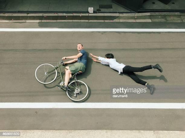 femme et homme sur vélo allongé sur le sol - velo humour photos et images de collection