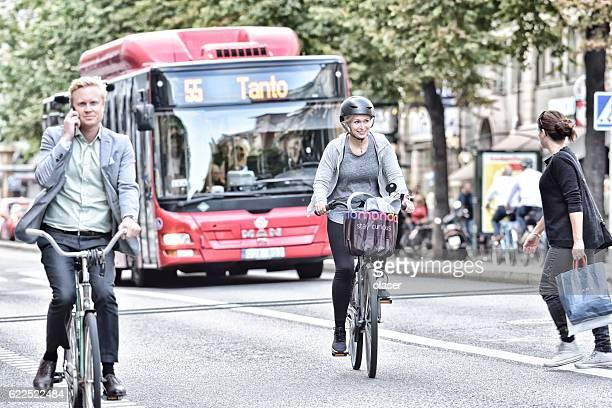 woman and man on bicycles in traffic, bus in background - rijwiel stockfoto's en -beelden